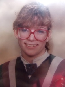 High school graduation photo with giant, red glasses